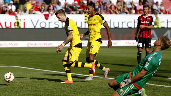 Borussia Dortmund's Marco Reus (L) and Pierre-Emerick Aubameyang (C) celebrate a goal against FC Ingolstadt's goalkeeper Oerjan Nyland during their Bundesliga first division soccer match in Ingolstadt, Germany August 23, 2015. REUTERS/Michaela RehleDFL RULES TO LIMIT THE ONLINE USAGE DURING MATCH TIME TO 15 PICTURES PER GAME. IMAGE SEQUENCES TO SIMULATE VIDEO IS NOT ALLOWED AT ANY TIME. FOR FURTHER QUERIES PLEASE CONTACT DFL DIRECTLY AT + 49 69 650050